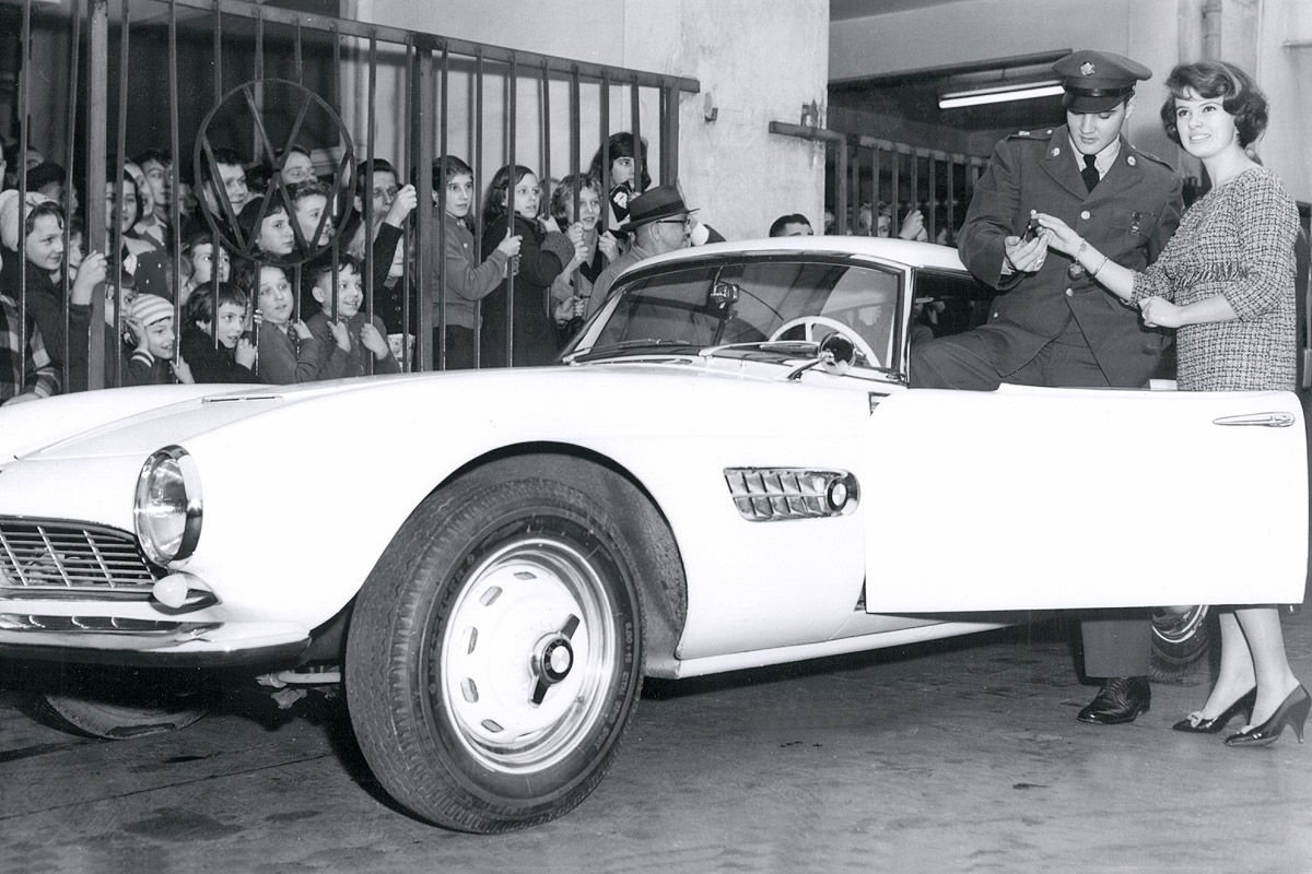 Elvis y su BMW 507. Se enamoró de el viendo correr a Hans Stuck con uno en Alemania. Cansado de borrar números de teléfono escritos con barra de labios en él, lo acabo pintando de rojo.
